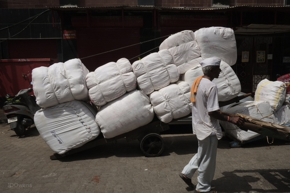 A workman walks past bails of fabric on a hand-cart in his ubiquitous Ghandi style garb and Nehru cap.